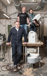 Das EOOS-Team (v.l.n.r.): Martin Bergmann, Harald Gründl und Gernot Bohmann von EOOS mit dem save! Trenn-WC aus der Produktion von Keramik Laufen. Foto: Carolina Frank