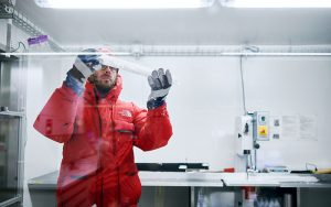 Ein Berner Forscher inspiziert das Segment eines Eiskerns im Tiefkühl-Labor der Universität Bern. Foto: Manu Friederich