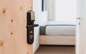 Elektronischer PIN-Code-Beschlag von SALTO an einer Hotelzimmertür in der Revier Mountain Lodge Adelboden. Die Gäste haben per PIN, Mitarbeiter per Mobile Access oder Chip Zutritt. Foto: REVIER Hospitality Group