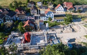 Das Mehrfamilienhaus in Huttwil enthält einen Warmwasserspeicher (roter Tank) mit 110 m³ Fassungsvermögen; er bringt die Solarwärme von den Sommermonaten ins Winterhalbjahr. Fotos: Jenni Energietechnik AG