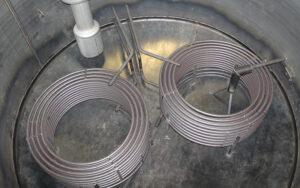 Die Frostschutzflüssigkeit aus dem Solarkreislauf durchströmt die spiralförmigen Rohre. Sie dienen als Wärmetauscher, welche die Solarwärme in den saisonalen Speicher übertragen